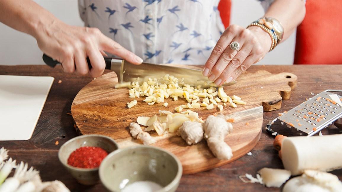 cortar la raíz de jengibre crudo en una tabla de cortar de madera