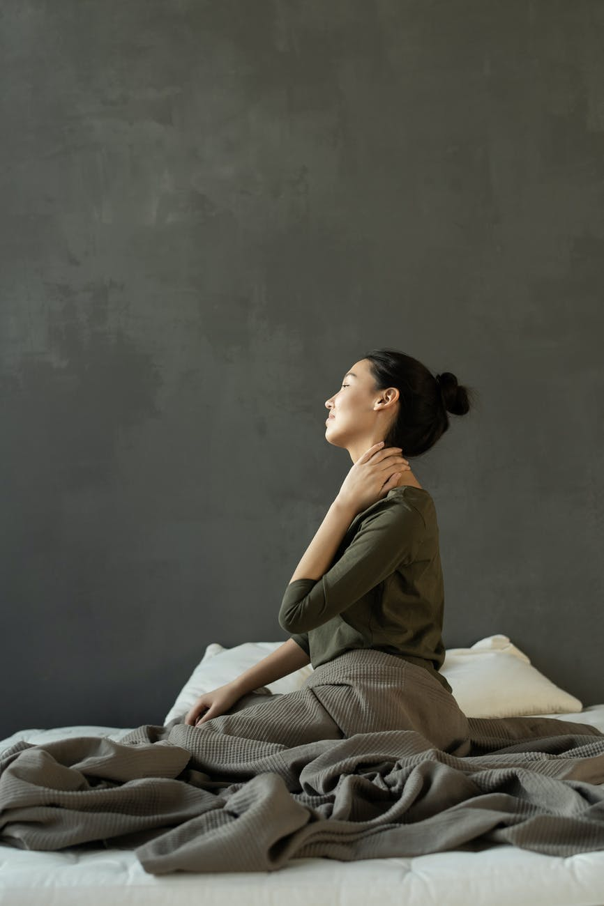 woman in gray dress sitting on bed